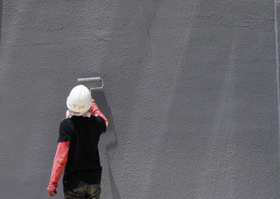 Man painting with a roller an exterior wall in grey
