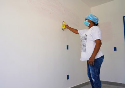 Woman wearing a facemask, applying sheetrock on the interior walls of an apartment